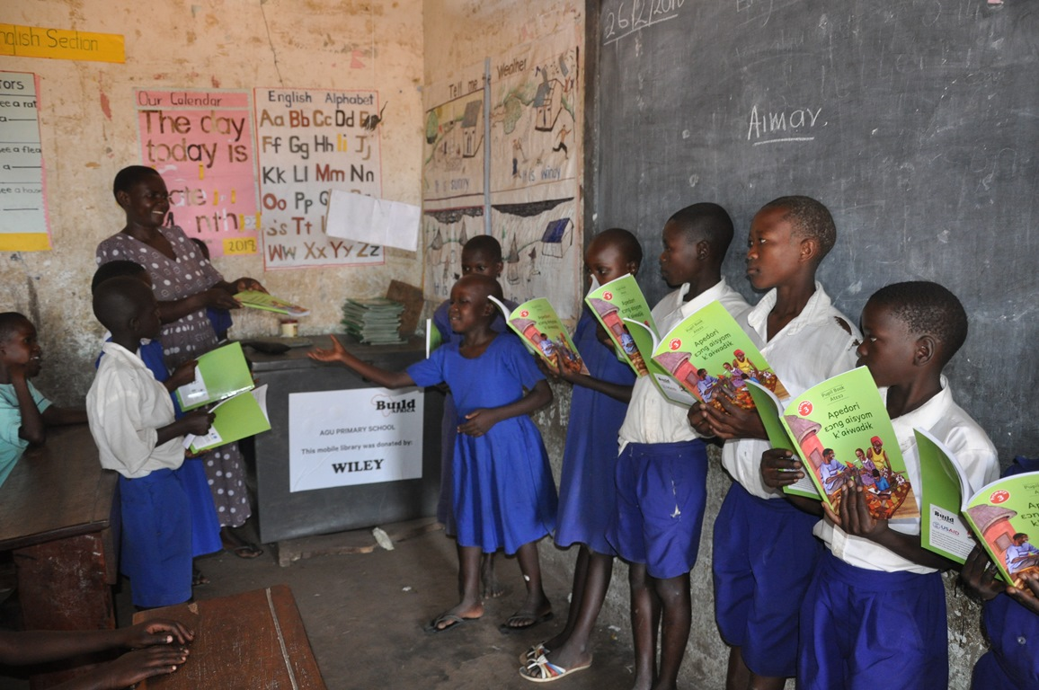 Children receiving books from the ILEAP project