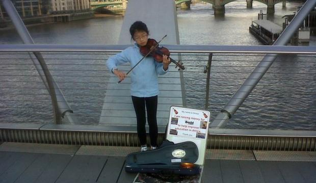 Young girl playing the violin on a bridge for Build Africa
